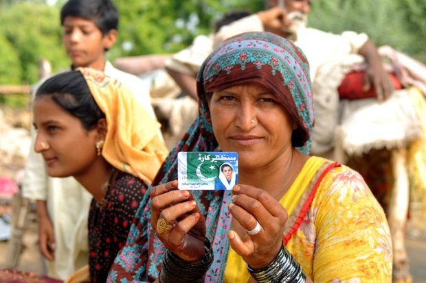 A woman displays her debit card provided under Pakistan's national income support programme.